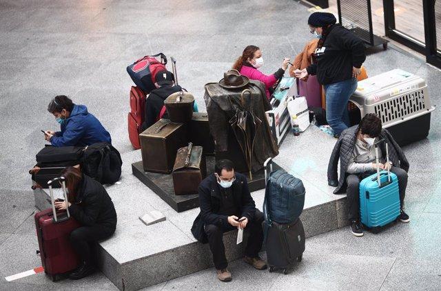 Viajeros esperan en un asiento de la estación de tren de Atocha, a 15 de marzo de 2021.