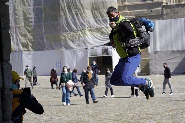 Un peregrino se fotografía saltando en la Catedral de Santiago durante el puente de San José, en Santiago de Compostela.