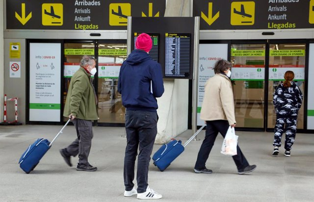 21 March 2021, Spain, Palma: A man stands at the exits for arriving flights at Palma de Mallorca airport. Airlines plan from Sunday after a long forced break to bring the first holiday makers from Germany to Majorca again. Photo: Clara Margais/dpa
