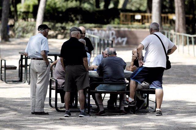 Archivo - Varios pensionistas juegan al dominó en un parque de Madrid.