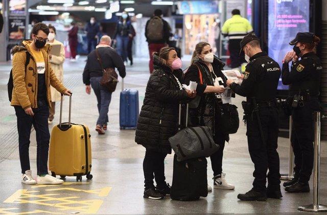 Agentes de la Policía Nacional piden justificantes durante controles de movilidad en la estación de tren de Atocha, en Madrid (España), a 26 de marzo de 2021.