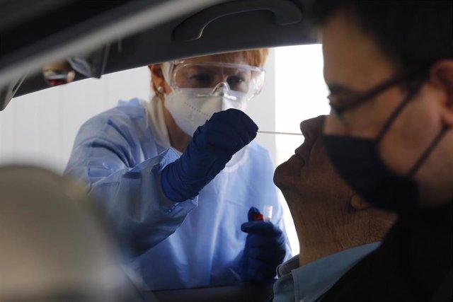 """Archivo - La enfermera Fátima Montero Embil realiza test PCR para la detección del COVID-19 en el """"Autocovid"""" del Hospital Universitario Central de Asturias (HUCA), Oviedo."""