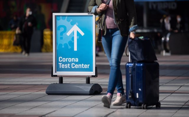 "26 March 2021, Bavaria, Munich: A woman passes past a sign with the inscription ""Corona Test Center"" at Munich airport as Germany will require Covid-19 tests on flight arrivals starting from Sunday. Photo: Sven Hoppe/dpa"