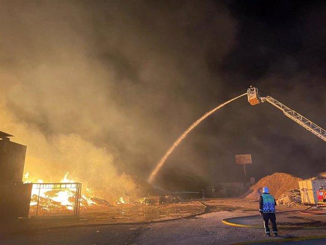 Bomberos trabajando en la extinción de un incendio en una planta de reciclaje de palets de madera en Cubas de la Sagra (Madrid)
