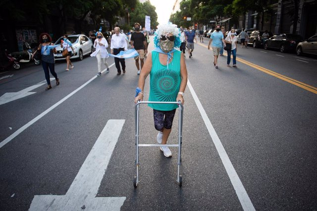 27 February 2021, Argentina, Buenos Aires: A protester with a walker takes part in a protest against the Argentinian government after the VIP vaccine rollout scandal. The government published a list of 70 public figures who have already received the coron