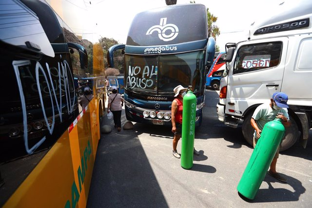 17 March 2021, Peru, Lima: People walk with oxygen tanks and try to find a way to refill their oxygen while transportation completely stopped as trucks drivers block the Central Highway from Ate to Chaclacayo during their two days strike. Photo: -/GDA via