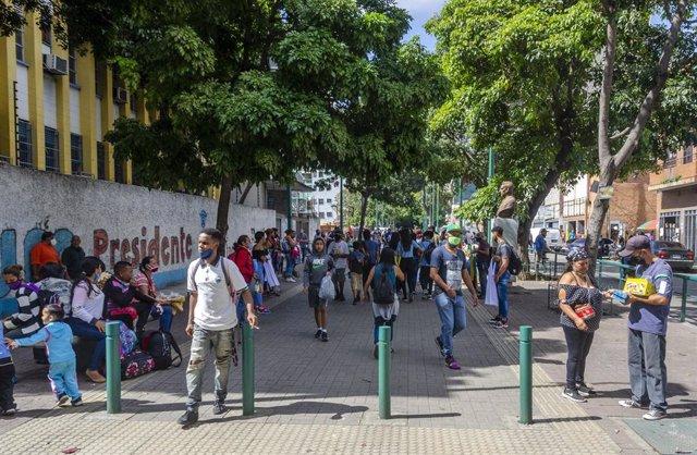 Archivo - Personas con mascarillas en una calle de Caracas