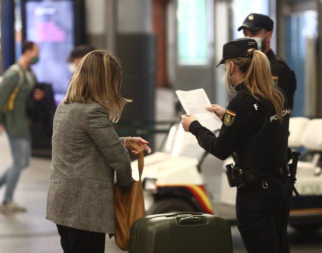 Agentes de la Policía Nacional piden justificantes durante controles de movilidad en la estación de tren de Atocha, en Madrid (España), a 26 de marzo de 2021