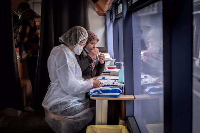 Archivo - 22 February 2021, France, Saint-Etienne: A patient sits next to a medical worker in protective clothing as she gives a sample for a Corona test at a testing station on a bus. The second mass testing campaign to contain the Corona pandemic is und