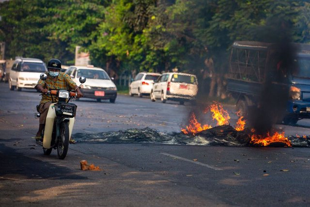 25 March 2021, Myanmar, Yangon: A man rides his motorcycle next to burning tyres during a demonstration against the military coup and the detention of civilian leaders. Photo: Theint Mon Soe/SOPA Images via ZUMA Wire/dpa