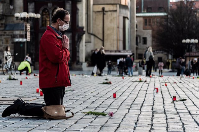 26 March 2021, Czech Republic, Prague: A man kneels on the ground to offer prayers along the slabs lining Prague's Old Town Square, which has been decorated with crosses in remembrance of those who died after contracting coronavirus. Photo: Tomas Tkacik/S