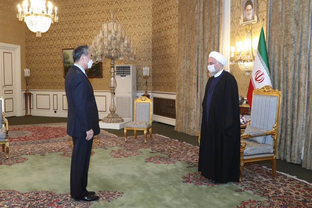 HANDOUT - 26 March 2021, Iran, Tehran: Iranian President Hassan Rouhani (R) receives Chinese Foreign Minister Wang Yi prior to their meeting. Photo: -/Iranian Presidency/dpa - ATTENTION: editorial use only and only if the credit mentioned above is referen