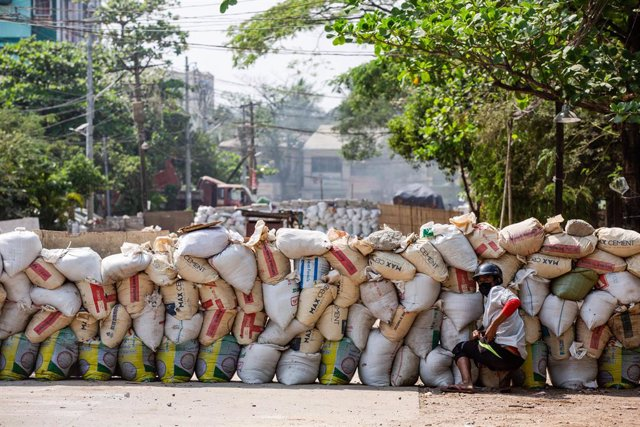 19 March 2021, Myanmar, Yangon: A protester takes cover behind a makeshift barricade during a protest against the military coup and the detention of civilian leaders. Photo: Aung Kyaw Htet/SOPA Images via ZUMA Wire/dpa
