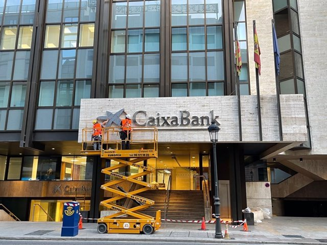 Operarios colocan el logo de CaixaBank en el edificio que albergaba la sede de Bankia en València