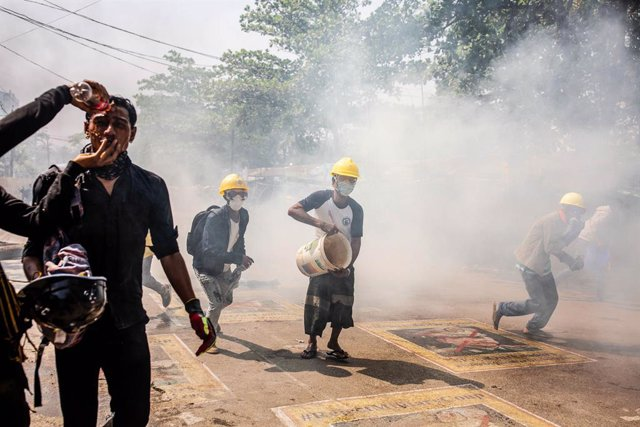 19 March 2021, Myanmar, Yangon: Demonstrators run amid tear gas during clashes at a protest against the military coup and the detention of civilian leaders. Photo: Aung Kyaw Htet/SOPA Images via ZUMA Wire/dpa