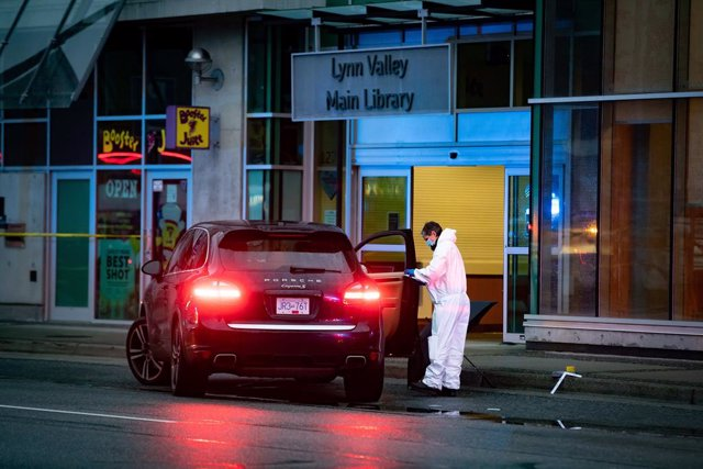 27 March 2021, Canada, North Vancouver: A forensics police officer collects evidence outside the entrance to the Lynn Valley Library. A woman is dead and six others injured after a stabbing on Saturday that police said they were trying to determine a moti