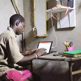 Archivo - Un niño en Senegal carga una tablet con un kit solar fotovoltaico