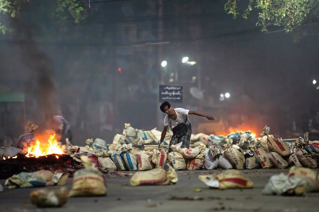 27 March 2021, Myanmar, Yangon: A demonstrator stacks bags on a street as a barricade during a demonstration against the military coup and the detention of civilian leaders. Photo: Theint Mon Soe/SOPA Images via ZUMA Wire/dpa
