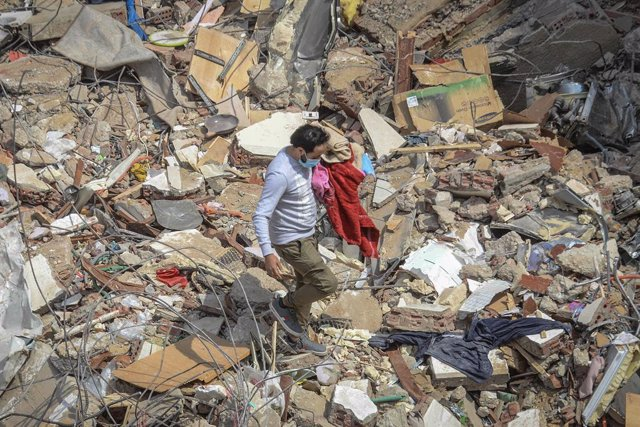 27 March 2021, Egypt, Cairo: A civilian carries his belongings at the site where a multi-storey building collapsed in Gesr al-Suez district. Egyptian media said the collapsing killed at least eight people and injured two dozen. Photo: Tarek Wajeh/dpa