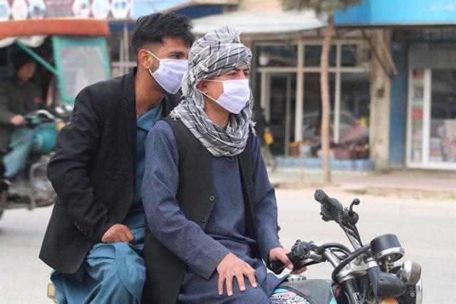 Dos hombres con mascarilla en una moto en la provincia de Yauzyán, en Afganistán