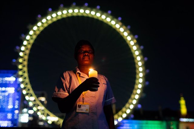 23 March 2021, United Kingdom, London: Nurse Sanyu Kasule stands at the London Eye in London to mark the National Day of Reflection, on the anniversary of the first national lockdown to prevent the spread of coronavirus. Photo: David Parry/PA Wire/dpa