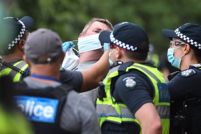 Archivo - Police attempt to put a mask on an arrested protester during an anti-vaccination rally in Melbourne, Saturday, February 20, 2021. The national rollout of the Pfizer vaccine will begin on Monday in what will be the largest exercise of its kind in