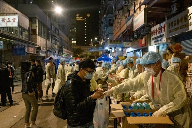 Archivo - 04 February 2021, China, Hong Kong: Health workers wearing personal protective equipment distribute drinks to residents during the mandatory coronavirus testing. Photo: Isaac Wong/SOPA Images via ZUMA Wire/dpa