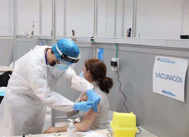 Archivo - Una mujer recibe la vacuna de AstraZeneca contra el COVID-19, en el Pabellón 3 del Hospital Público Enfermera Isabel Zendal, en Madrid, (España), a 23 de febrero de 2021.