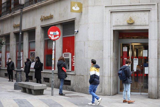 Archivo - Varias personas esperan en una cola respectando la distancia de seguridad para entrar en una sucursal del Banco Santander en Madrid.