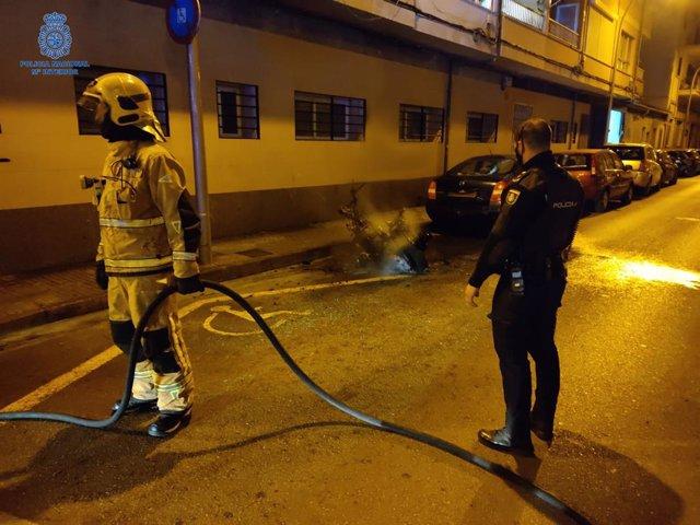 Un agente de la Policía Nacional y un bombero, junto a la motocicleta quemada.