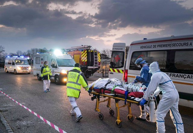 Archivo - 29 March 2020, France, Mulhouse: Emergency medical personnel transport a patient infected with the coronavirus from a military hospital to an ambulance to be transferred to another hospital by a TGV high-speed train. Photo: Sebastien Bozon/AFP/d