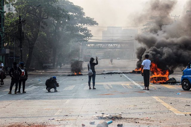 27 March 2021, Myanmar, Yangon: People stand near burning tires on the street during a demonstration against the military coup and the detention of civilian leaders. Photo: Santosh Krl/SOPA Images via ZUMA Wire/dpa