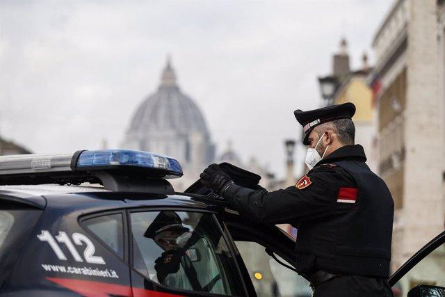 Archivo - 24 December 2020, Italy, Rome: ACarabinieri police officer checks the documents of drivers at a checkpoint near St. Peter's Basilica amid the Coronavirus lockdown during Christmas. Photo: Cecilia Fabiano/LaPresse via ZUMA Press/dpa