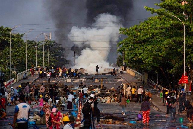 Enfrentamiento entre manifestantes y fuerzas de la junta militar en una jornada de protestas en Rangún, Birmania.