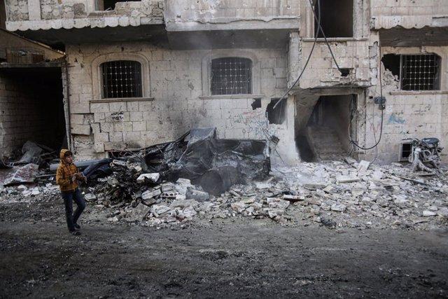 Archivo - Un niño camina frente a un edifico bombardeado en la provincia de Idlib, en el noroeste de Siria