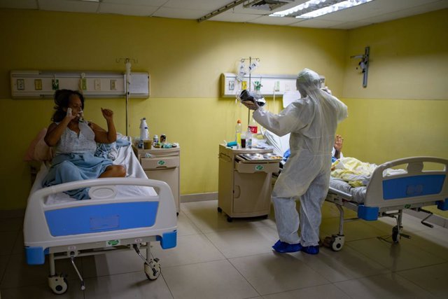 25 March 2021, Venezuela, Caracas: A health worker greets Covid-19 patients while using a small loudspeaker playing and music to try to raise good spirits in the ICU ward. Photo: Rafael Hernandez/dpa