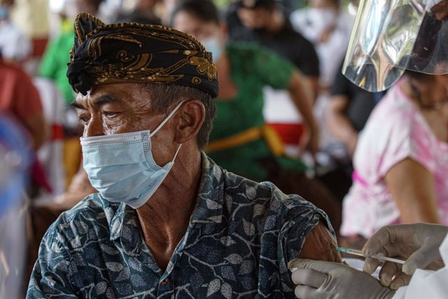 16 March 2021, Indonesia, Bali: A man receives a dose of a COVID-19 vaccine as part of a mass vaccination campaign. Photo: Dicky Bisinglasi/ZUMA Wire/dpa