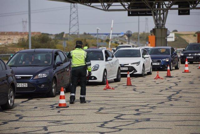 Un guardia civil de Tráfico da el alto durante un control en la carretera R5 km 20, en Madrid (España), a 26 de marzo de 2021. Un total de 4.818 efectivos de las Fuerzas y Cuerpos de Seguridad del Estado (FCSE) se desplegarán esta Semana Santa en la Comun