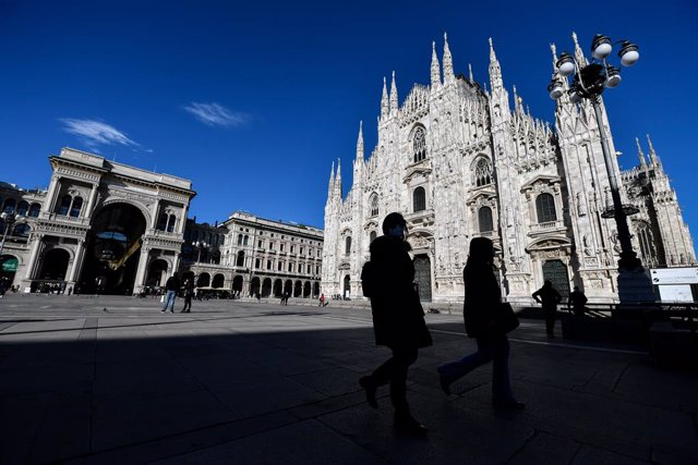 15 March 2021, Italy, Milan: Few pedestrians walk across the almost deserted Duomo square,on the first day of the newly reimposed restrictions to curb the spreading of coronavirus. Photo: Claudio Furlan/LaPresse via ZUMA Press/dpa