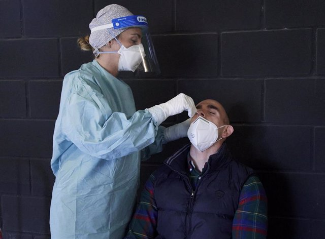 Archivo - Un trabajador sanitario realiza un test de antígenos a una persona en los Campos de Sport del Sardinero, en Santander,.