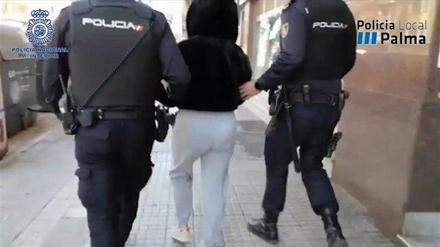 Dos policías escoltan a una persona detenida durante la operación contra un grupo organizado que vendía droga a domicilio en Palma.