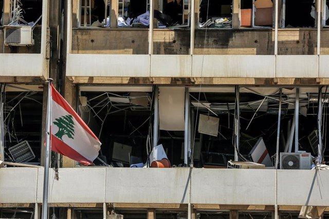 Archivo - Una bandera de Líbano frente a un edificio dañado por las explosiones en el puerto de Beirut