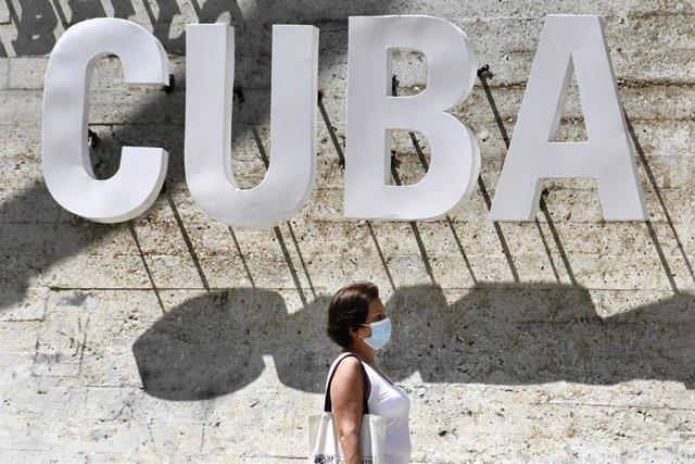 Una mujer con mascarilla pasea por La Habana