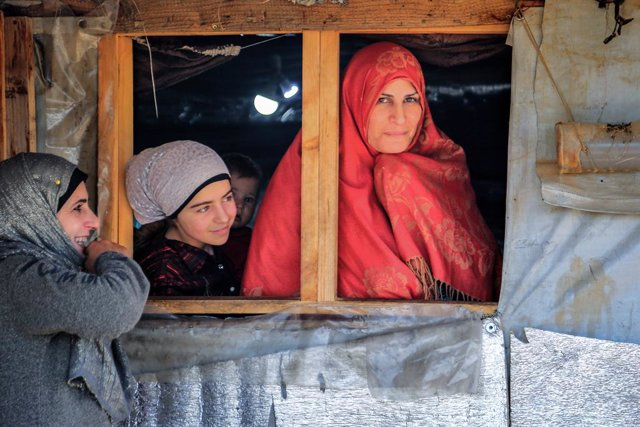 13 March 2021, Lebanon, Aarsal: A group of Syrian refugee women stand near a tent at the Barra refugee camp in the Lebanese town of Aarsal, located north-east of capital Beirut. UNICEF said that after 10 years since the start of the Syrian conflict, war h