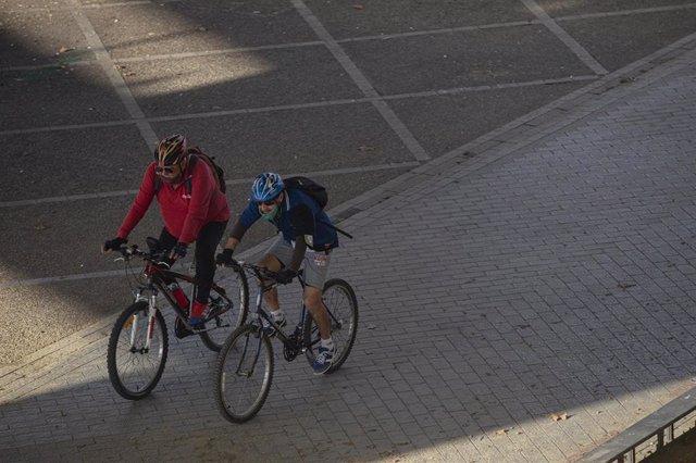 Archivo - Dos ciclistas con mascarilla