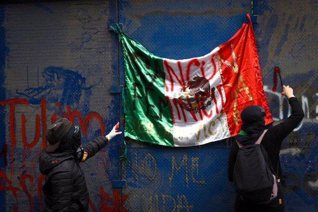 Manifestantes cuelgan una bandera contra los feminicidios tras el asesinator de la refugiada salvadoreñan Victoria Salazar.