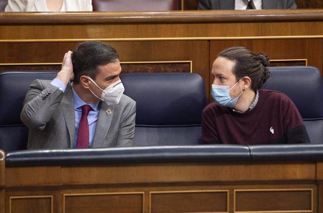 El presidente del Gobierno, Pedro Sánchez (i), conversa con el vicepresidente segundo del Gobierno, Pablo Iglesias, durante una sesión plenaria en el Congreso de los Diputados, Madrid, (España), a 24 de marzo de 2021. Este pleno, marcado por la campaña el