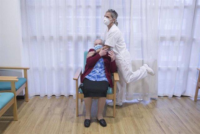 Archivo - Una enfermera con la primera usuaria de una residencia de Gijón en recibir la segunda dosis de la vacuna Pfizer-BioNTech contra el coronavirus.