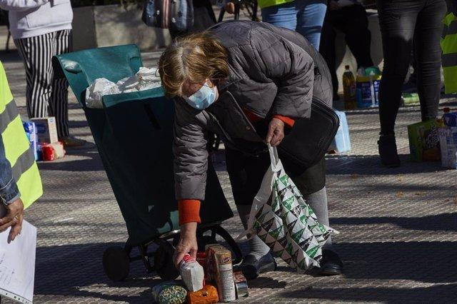 Una mujer recoge productos de alimentación donados por parte de la Despensa Solidaria de Chamberí (Madrid) durante la concentración y reparto de alimentos a familias vulnerables.