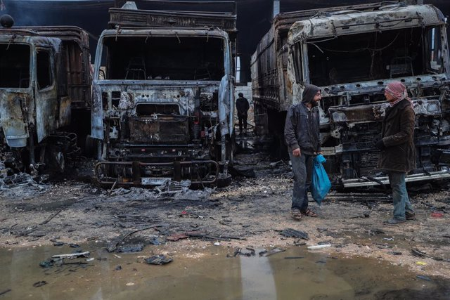 22 March 2021, Syria, Idlib: Syrians inspect the damage in the aftermath of an airstrike that was allegedly carried out by Russian warplanes on a truck depot near Bab al-Hawa border crossing on the Syrian-Turkish border. Photo: Anas Alkharboutli/dpa